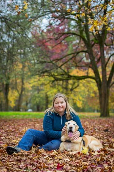 Person in blue sitting in fall leaves with yellow lab dog.