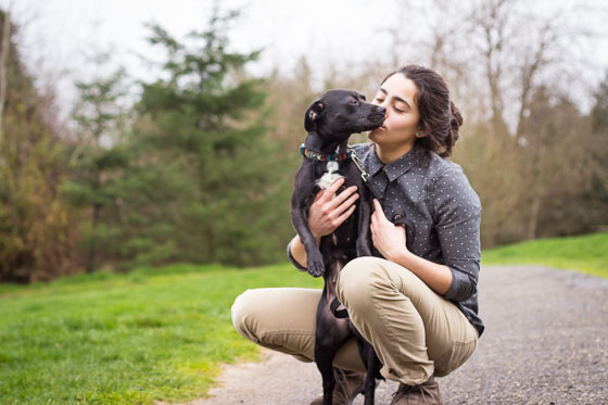 Person holding and kissing cute black puppy in a park.