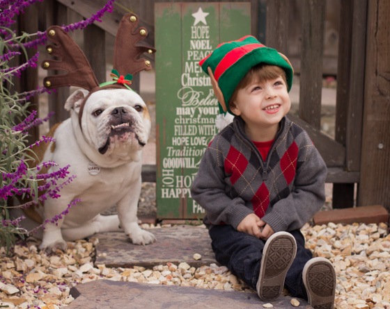 Child and bulldog wearing elf hat and antlers outside.