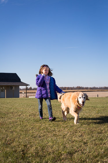 Child in purple coat with dog running in yard on a sunny day.