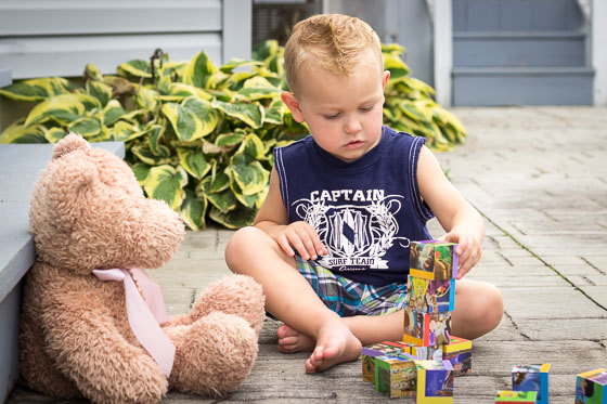 Small child in blue shirt outside playing with blocks and teddy bear.