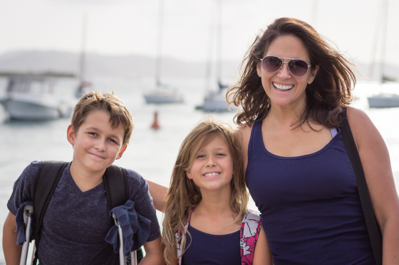 Close up of family with two children with sailboats in the background.