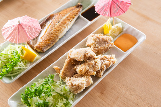 Filet of fish and fried chicken pieces displayed in narrow white dishes with sauces