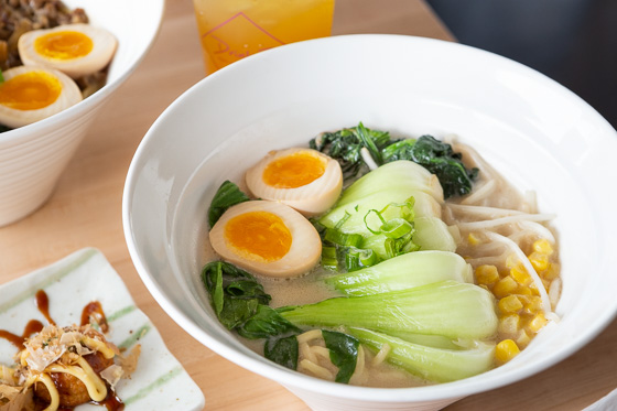white bowl of ramen with egg and bok choy