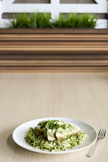 plate of chicken with noodles and pesto on a light colored table and simple grass accent