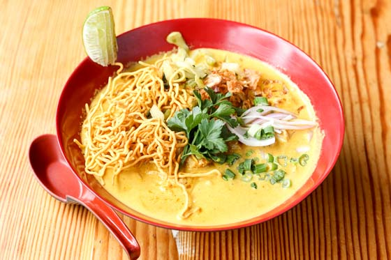 Khao Soi Thai noodle soup with yellow broth in a red bowl with red spoon.