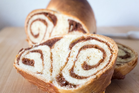 Close up of cinnamon swirl bread slice and loaf behind it.