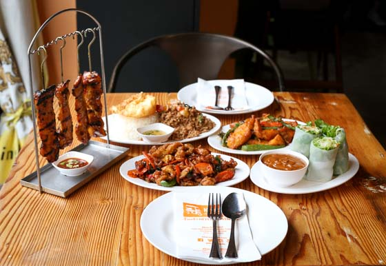 Restaurant table set for two with plates of Thai street food including ping chicken and fresh salad rolls.