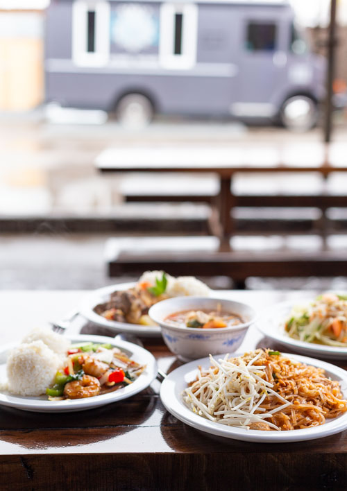 Several plates of Thai food on a wooden table with a purple food truck in the background.