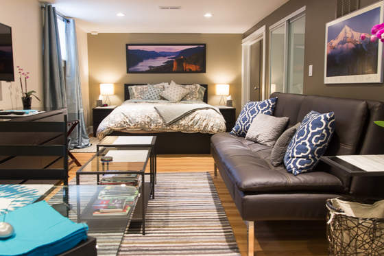 Studio apartment rental with styled bed, side tables, lamps, and couch.