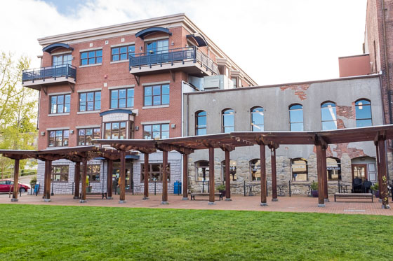 Commercial four story retail brick building with windows and an arbor, benches, and green grass in front.