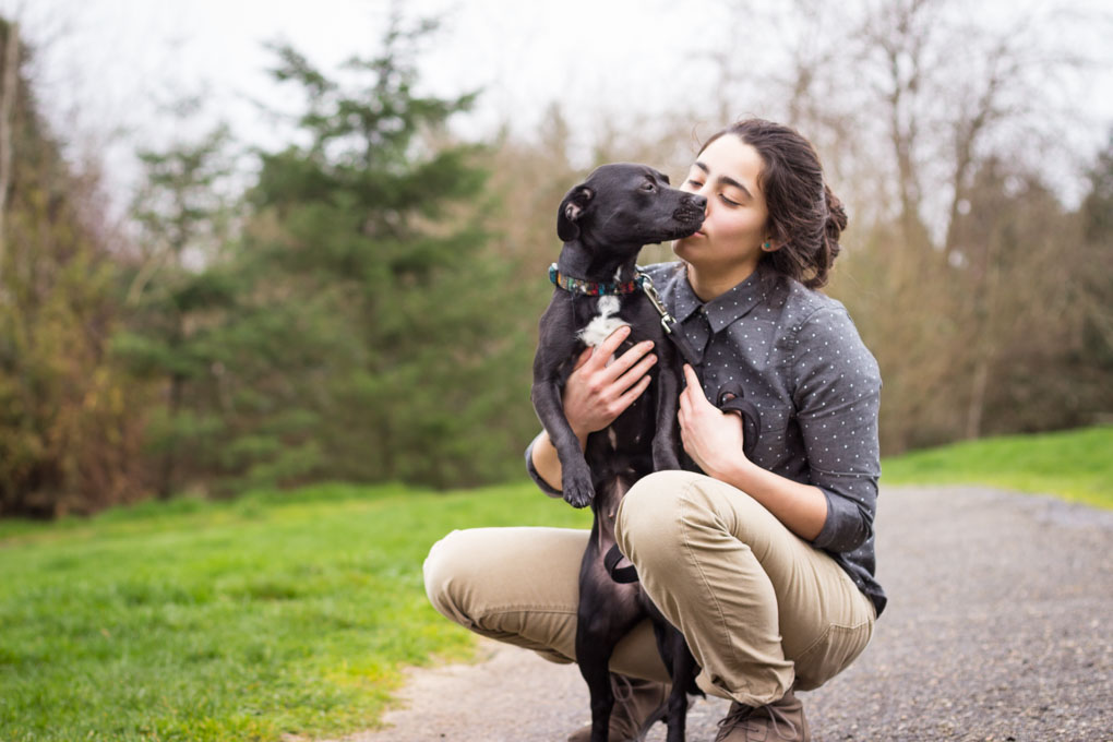 Person kissing black puppy dog in a park.