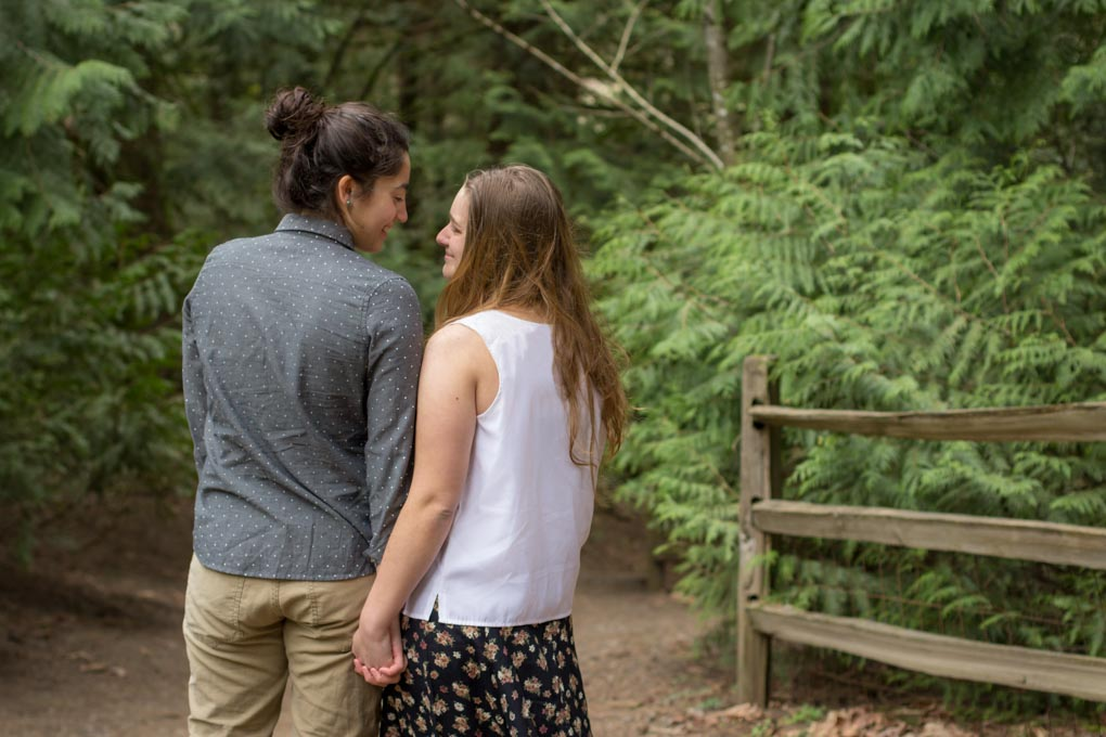 Couple with backs to camera holding hands and looking at each other in a park.