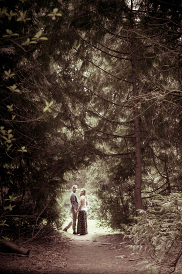 Couple in distance holding hands in the light seen through a tunnel of trees.