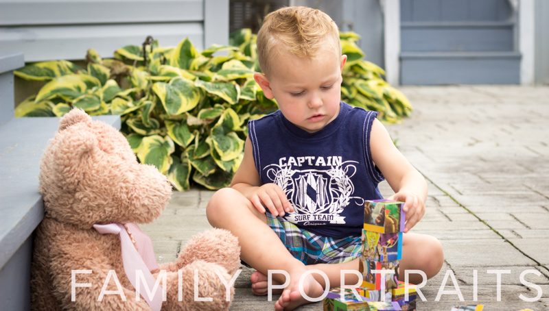 Small child in blue shirt and shorts with teddy bear and blocks on outside patio with plants in the background.
