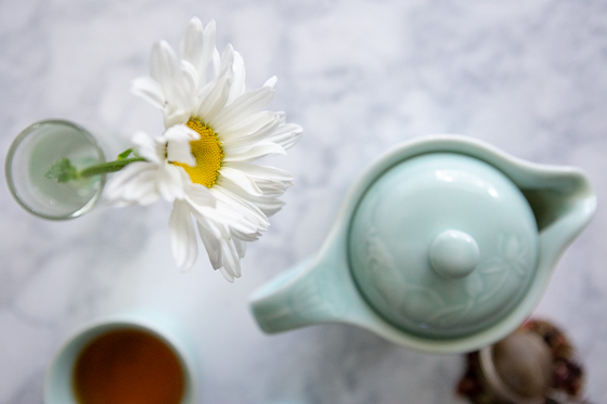 overhead shot of a teapot and flower on marble.