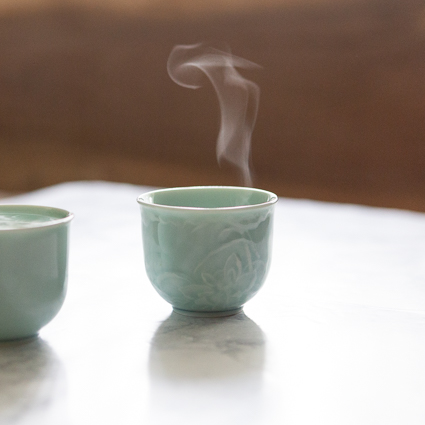 small green teacup with steam