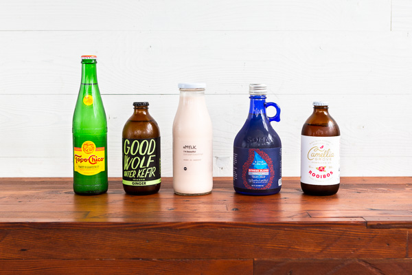 healthy bottled beverages lined up on a wood table