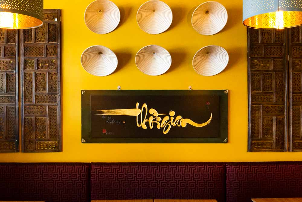 yellow wall with straw hats in Vietnamese restaurant