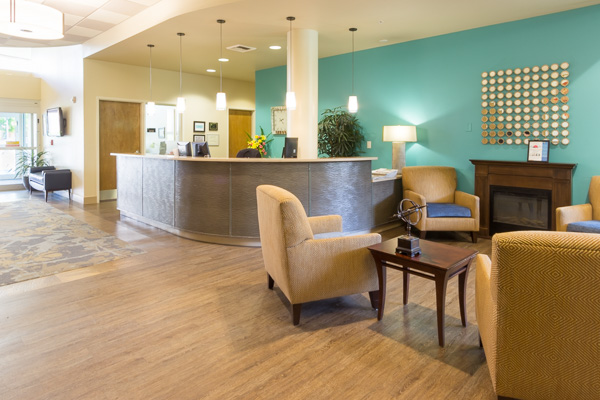 Brightly lit reception area with green wall and gold furniture