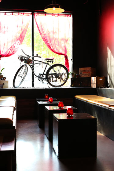 Cozy seating in restaurant with benches and a bike in the window backlit from sun