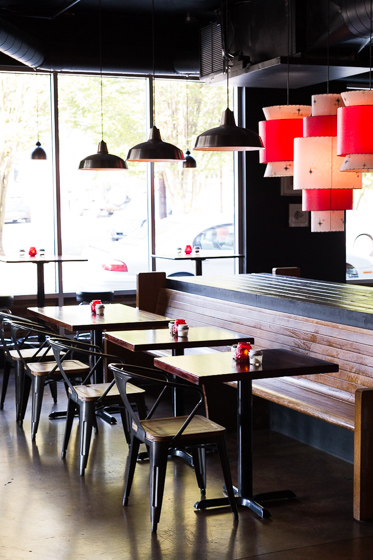 Darkly lit restaurant with iron and wood furniture and red lamps