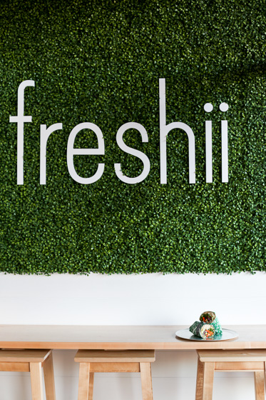 Wall of greenery with white Freshii lettering above a table and stools