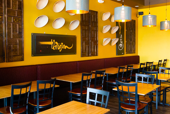 Dining area in Vietnamese restaurant with bright yellow walls and brown artwork
