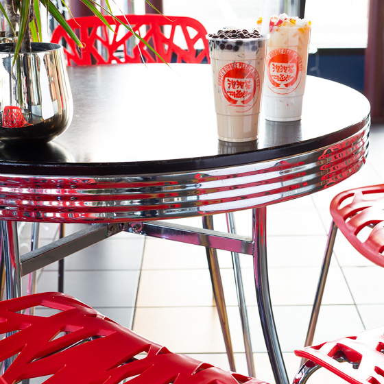 Two bubble tea drinks sitting on a chrome table with red chairs.
