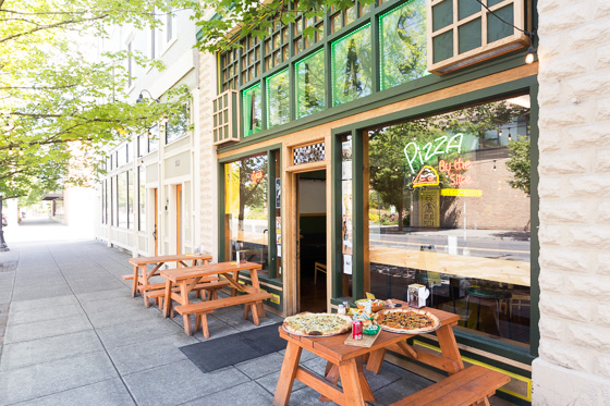 Sidewalk view of Atlas Pizza in Portland, Oregon with pizzas on picnic tables.