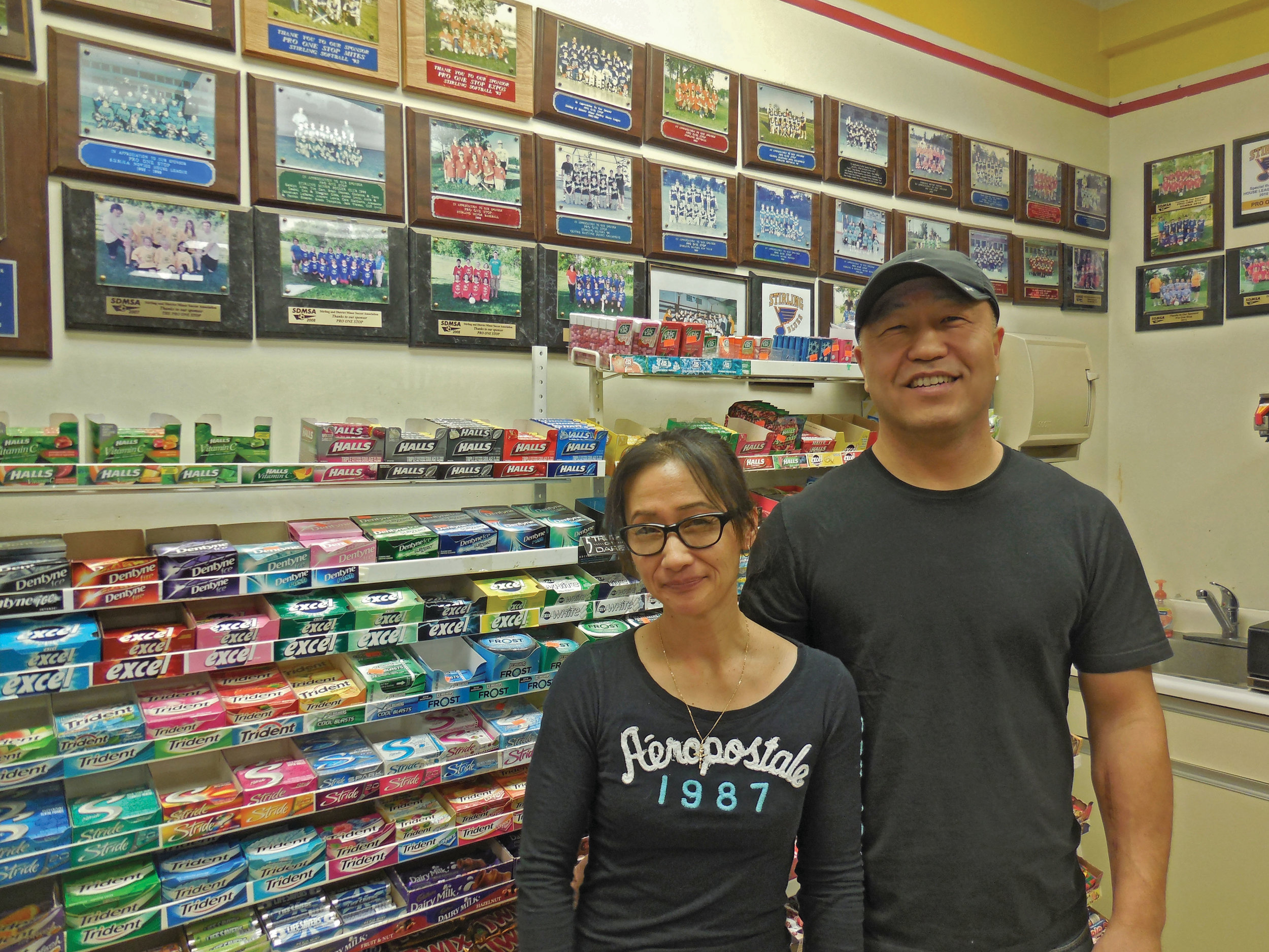 Current Pro One Stop proprietors Julie and Min Yoo stand in front of the photo wall, showing off the many local teams and events the family has proudly supported in Stirling.