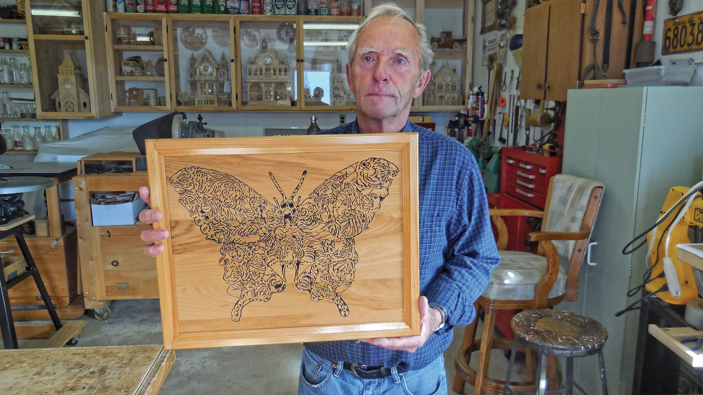 "Wood-worker Glen Finch shows off the intricate cut-out of a Tiger Butterfly, one of the most challenging pieces he has produced. ""I had to take a break and go back to it,"" he admits. Photo by Angela Hawn"