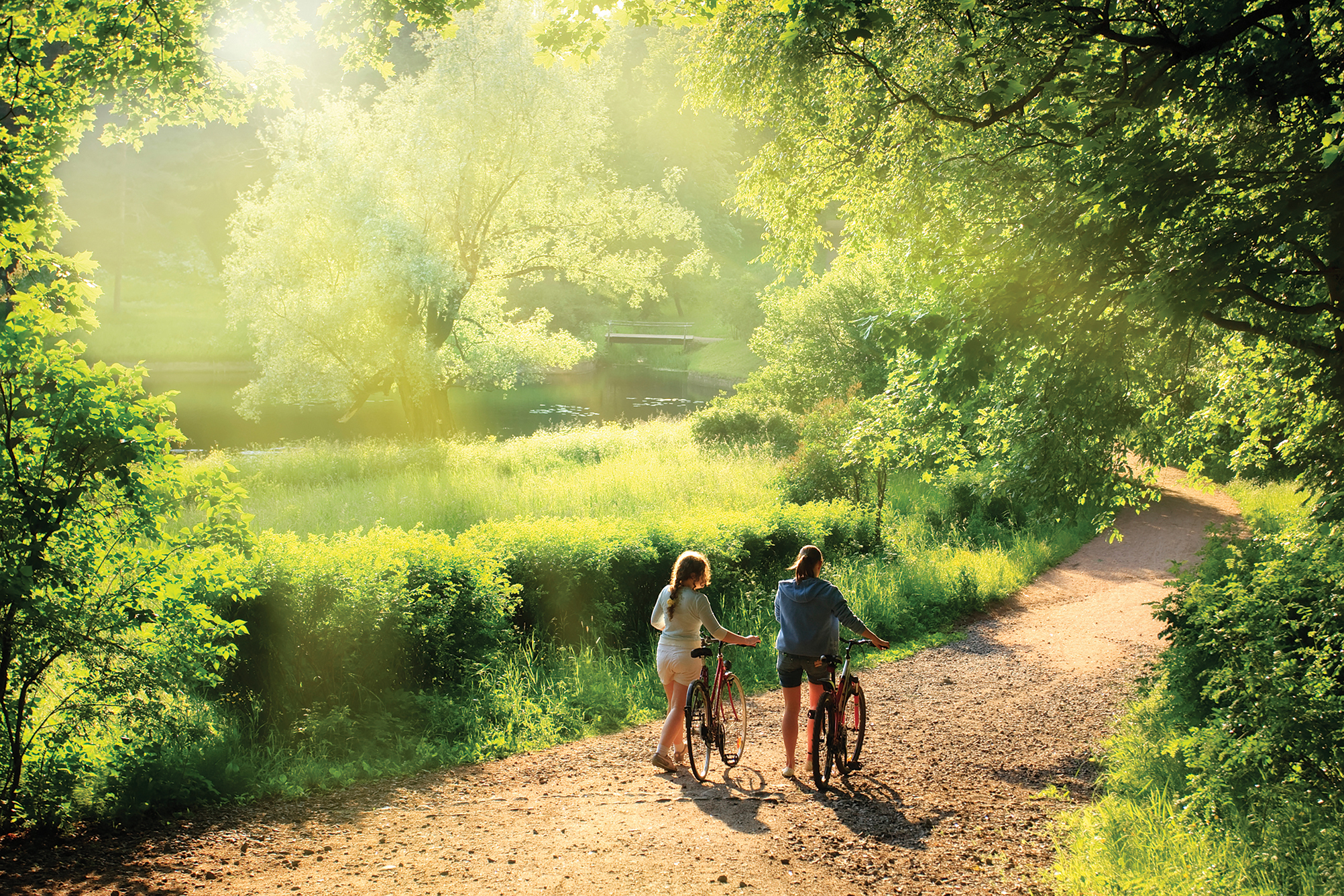 Taking a break from cycling, two children reconnect with nature as they walk along the trail. Photo courtesy Eastern Ontario Trails Alliance.