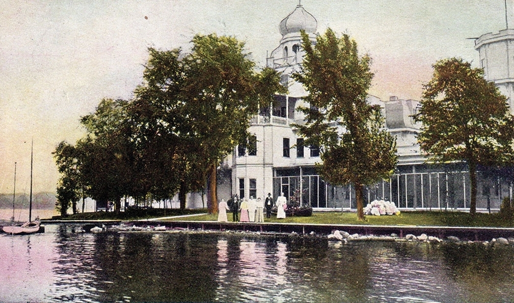 """As an IOF project in support of orphaned children, Oronhyatekha had Captain John's Island cleared of large black rat snakes and comfortable buildings erected, including a veritable mansion. Renamed """"Forester Island,"""" the site received its first visitors in 1894.  Tinted postcard, Penhale Collection."""