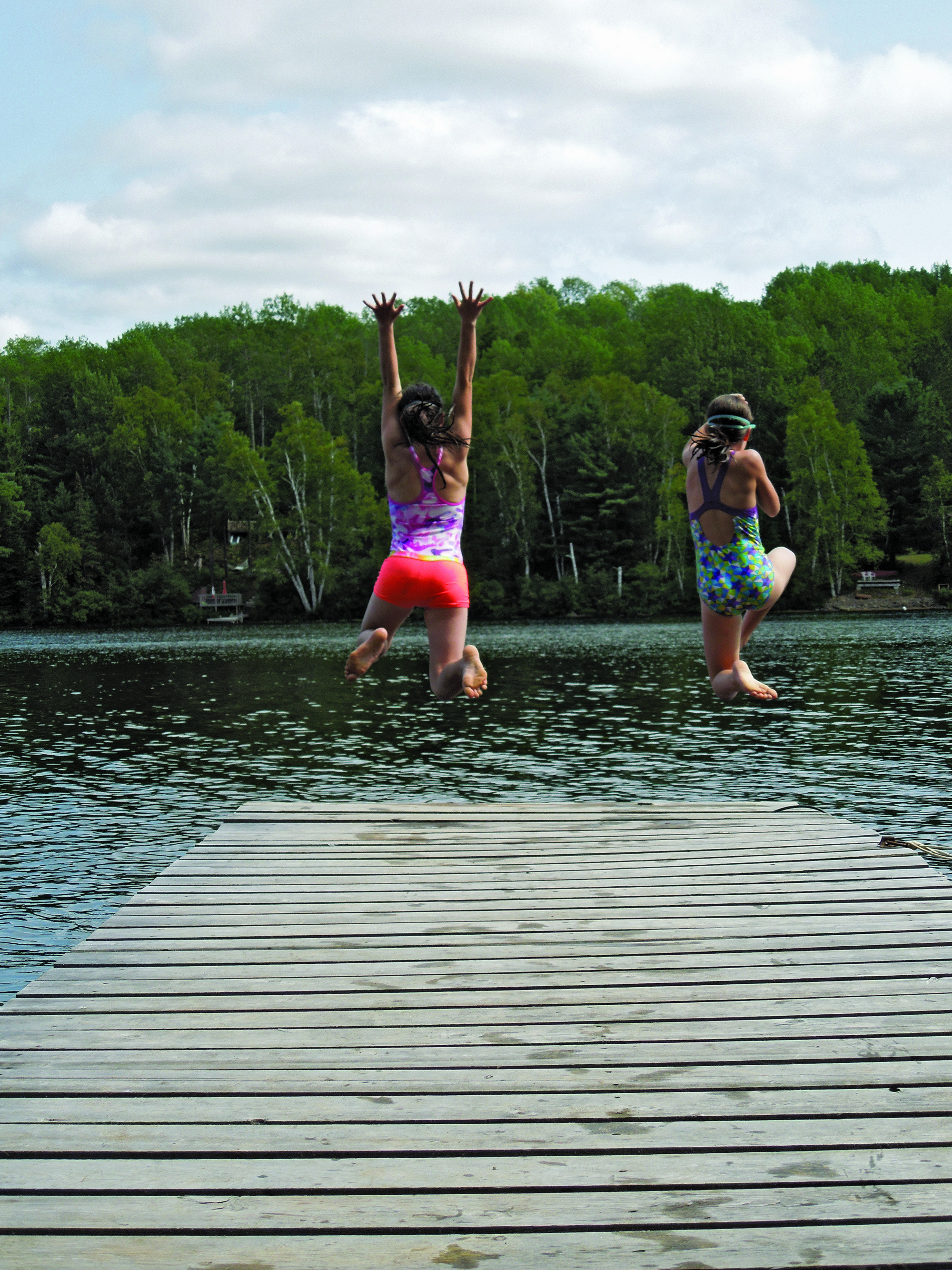2ND PLACE  – SUMMER SISTERS  Photographer: Heather Cowley  Photo Description: Sisters Sylvie and Kaelan were caught in this photo leaping off the dock into Lake St. Peter, Ontario.