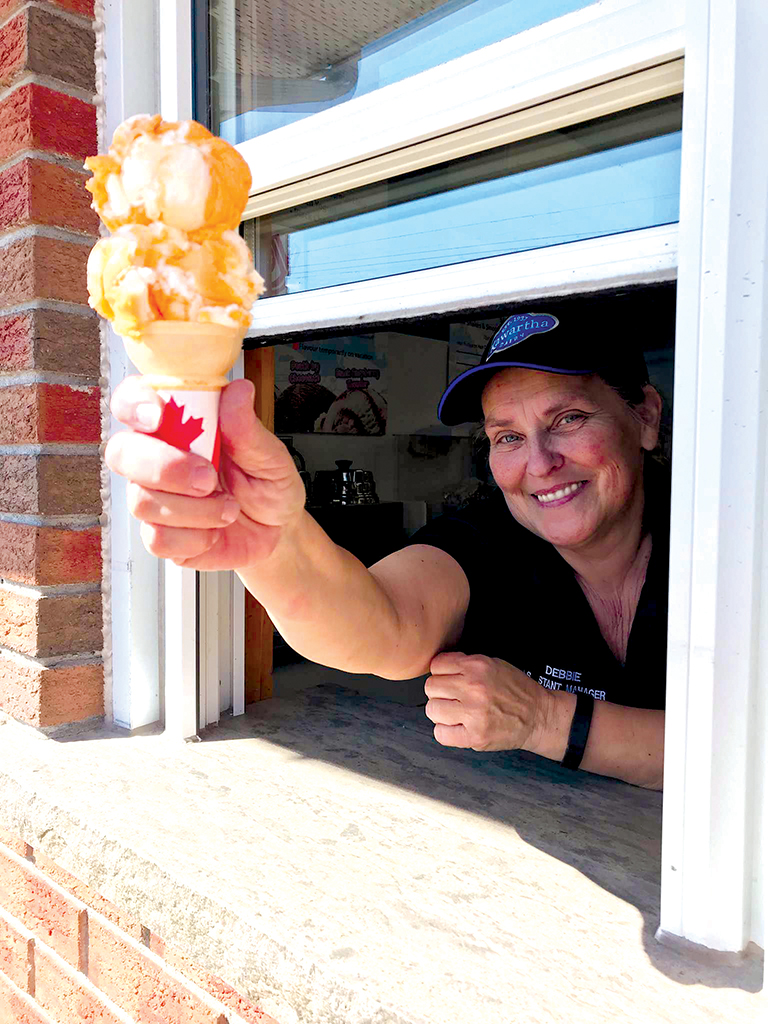 "Debbie is expert at dishing out the ""scoop"". Shown here with a cone of Tiger Tail ice cream, just one of the delicious flavours associated with summer vacations. Photo by James Kerr."