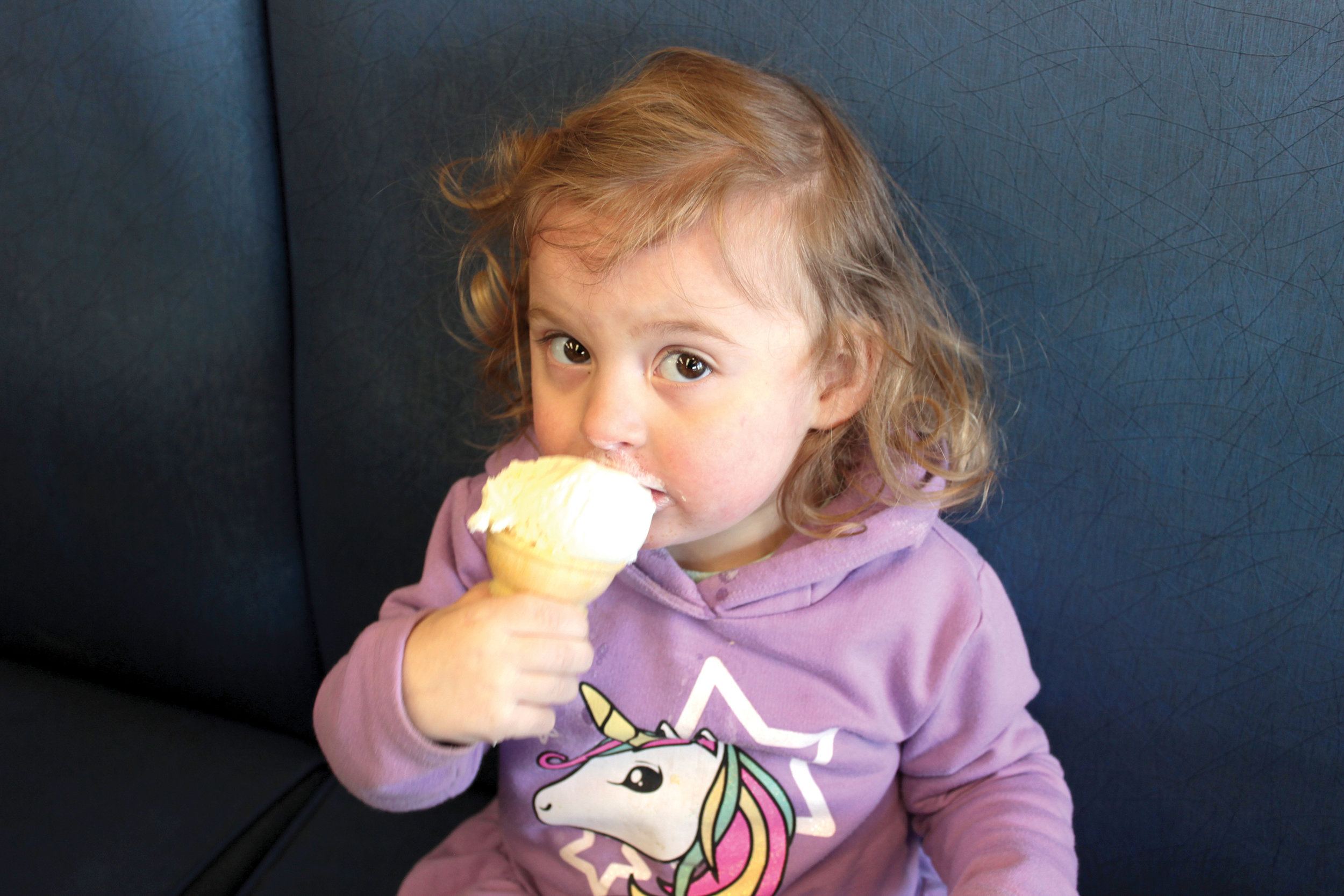 Boudica Kerr aged 2.5 is introduced to her first ice cream shop visit, with a much-negotiated and highly-compromised scoop of vanilla. Photo by James Kerr.
