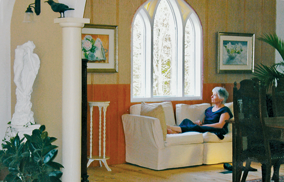 Now finished, the stained glass window becomes a showcase over a relaxing nook. Nancy Woodall shown here is enjoying the benefits of Patrick Nash's decision to move the window. Photo courtesy Nancy Woodall.