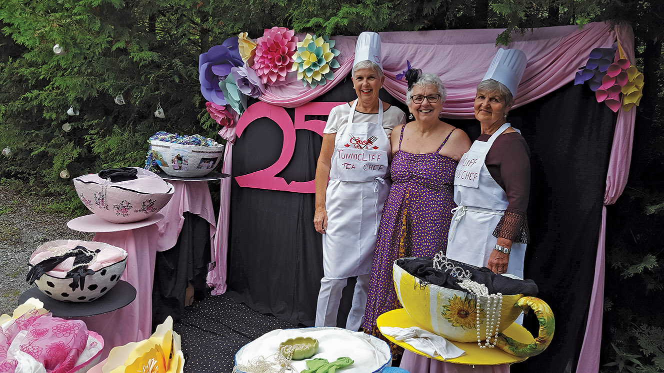 Judy Tunnicliff, centre, shown here with long time kitchen helper Mary Jo Brooks (Tweed) on the left and first timer Sue Ann Ducharme (Windsor) on the right. The humungous paper mache tea cups, shown in the foreground are the original creations of Mary Joe Brooks. Photo Courtesy Lorraine Gibson-Alcock