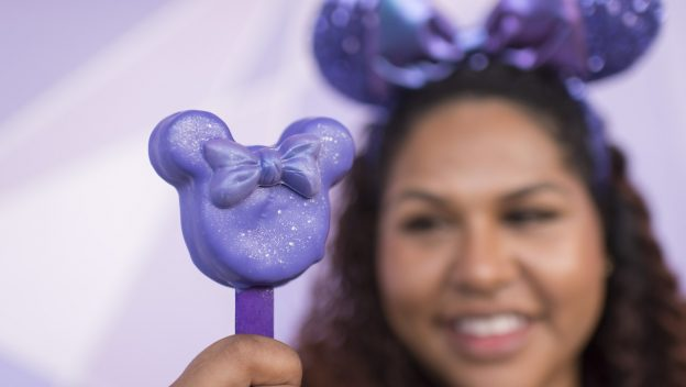 Purple Minnie Cake on a Stick    Magic Kingdom Park, Castle Hub Cart (available starting Jan. 11)  Minnie-shaped blackberry cake on a stick topped with a chocolate bow and coated in purple chocolate