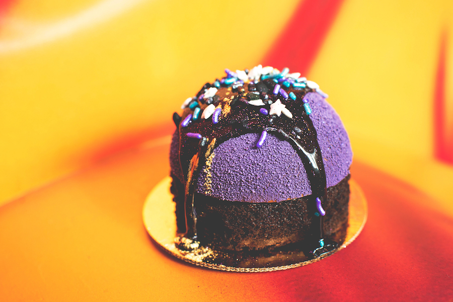 Purple Starry Sky Cake   Disney's All-Star Resorts, Food Courts  Purple chocolate mousse, chocolate sponge, and dark chocolate with a galaxy glaze topped with galaxy sprinkles