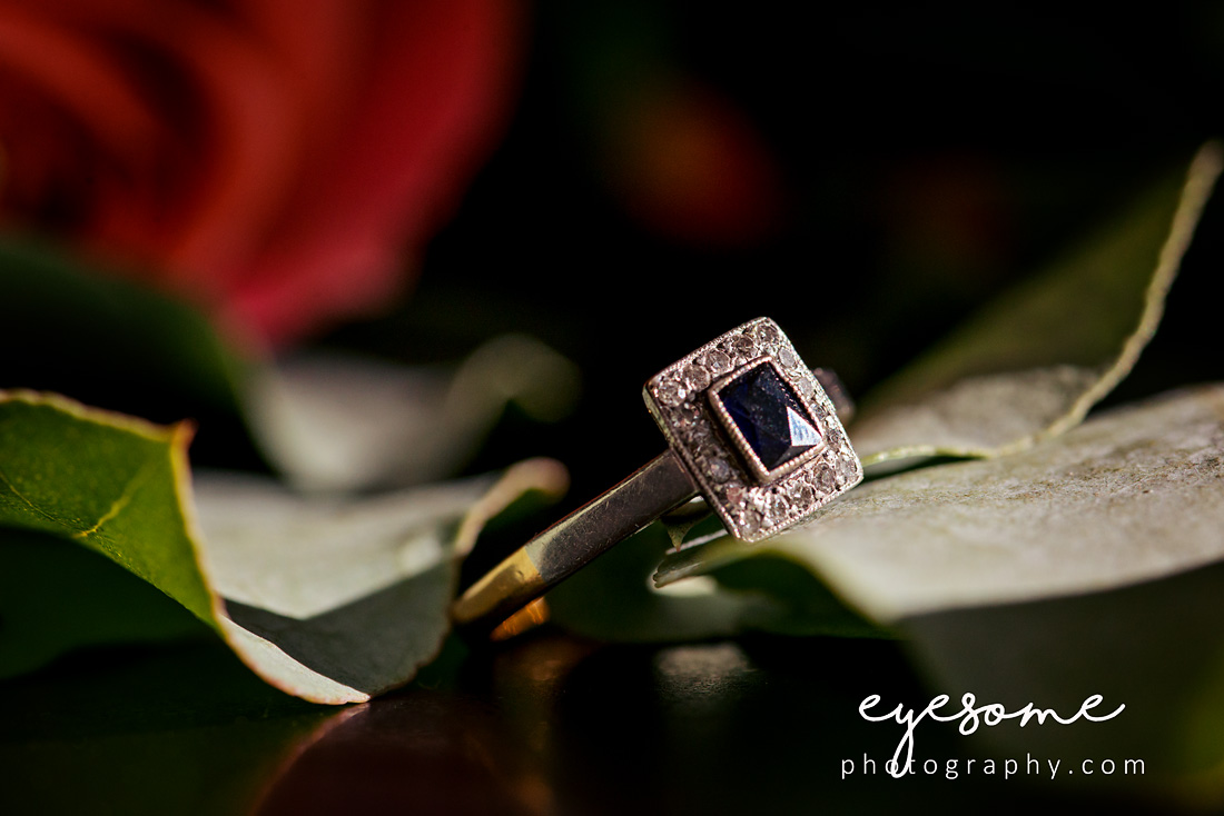 The engagement ring nestled amongst eucalyptus leaves to show off its vintage sparkle