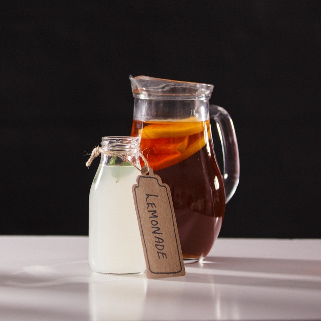 A display of homemade cloudy still lemonade with mint in a mini milk bottle with a brown tag saying Lemonade and a jug of freshly brewed iced tea with oranges.