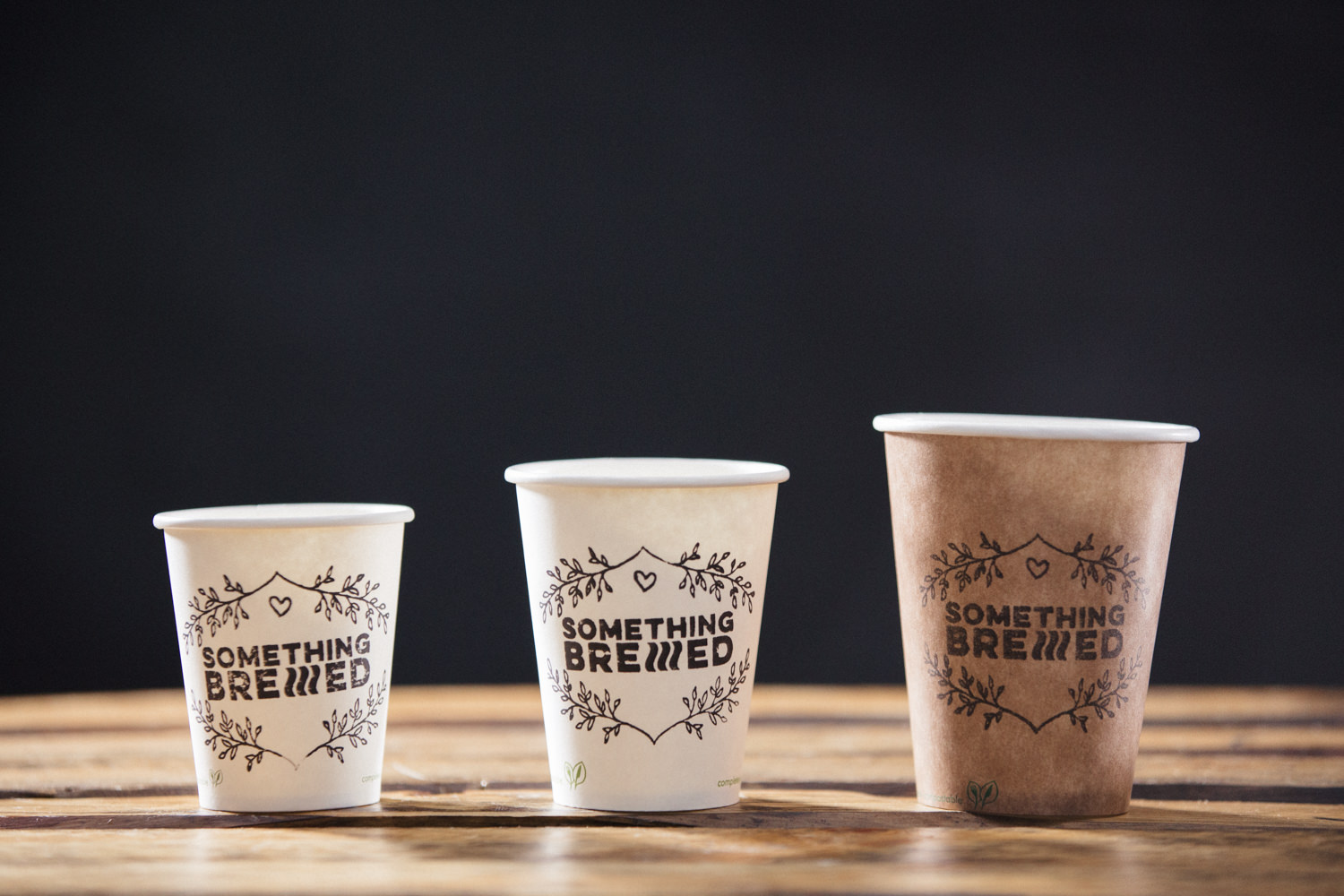 "Vegware fully compostable paper cups in 3 different sizes - 6oz 8oz and 12oz in white and brown with ""Something Brewed"" stamp"