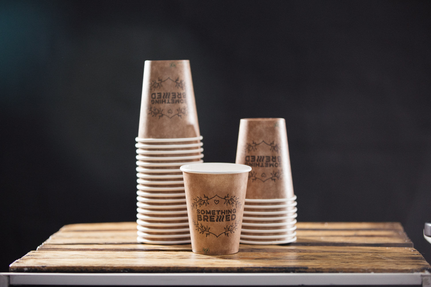 "Display of brown vegware cups with ""Something Brewed"" stamp on it."