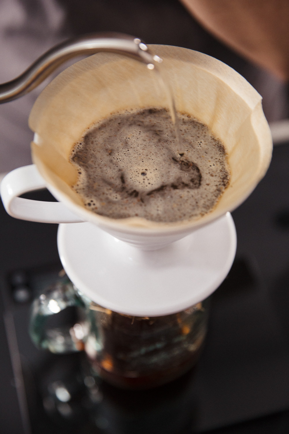 Pouring water from a gooseneck kettle into a V60 filter coffee set up using natural papers