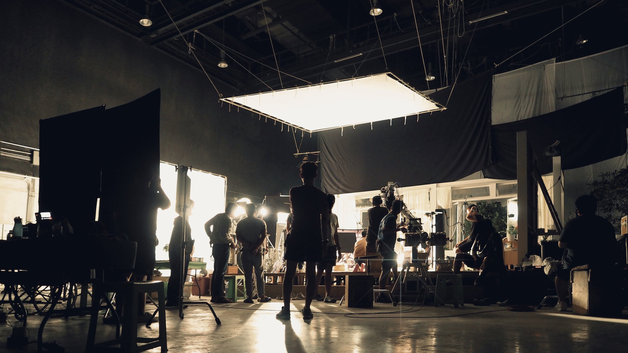 Behind the scenes of silhouette people working in big production studio with professional set and lighting for making movie film or video commercial.