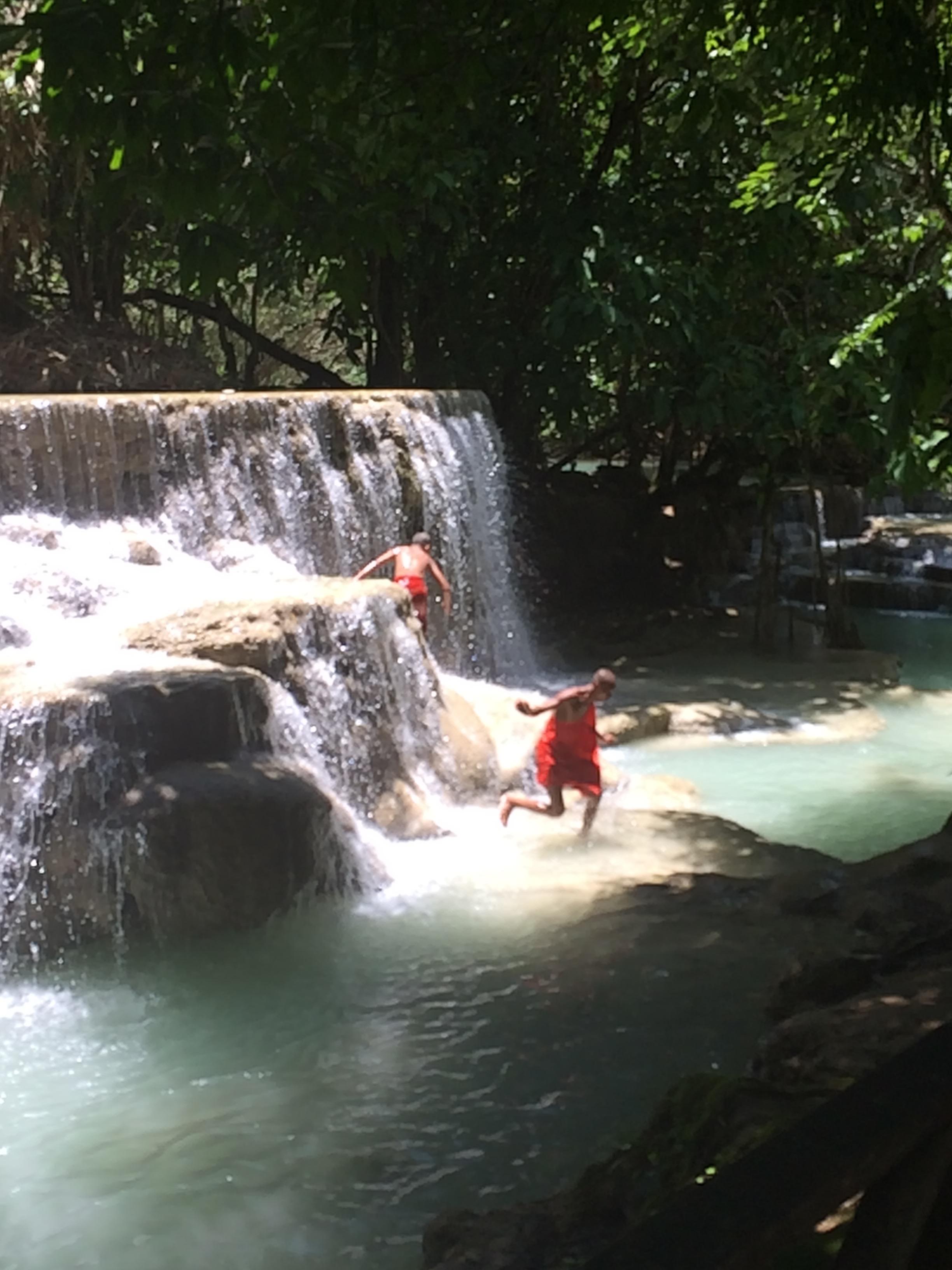 Monks playing in the waterfalls of Luang Prabang