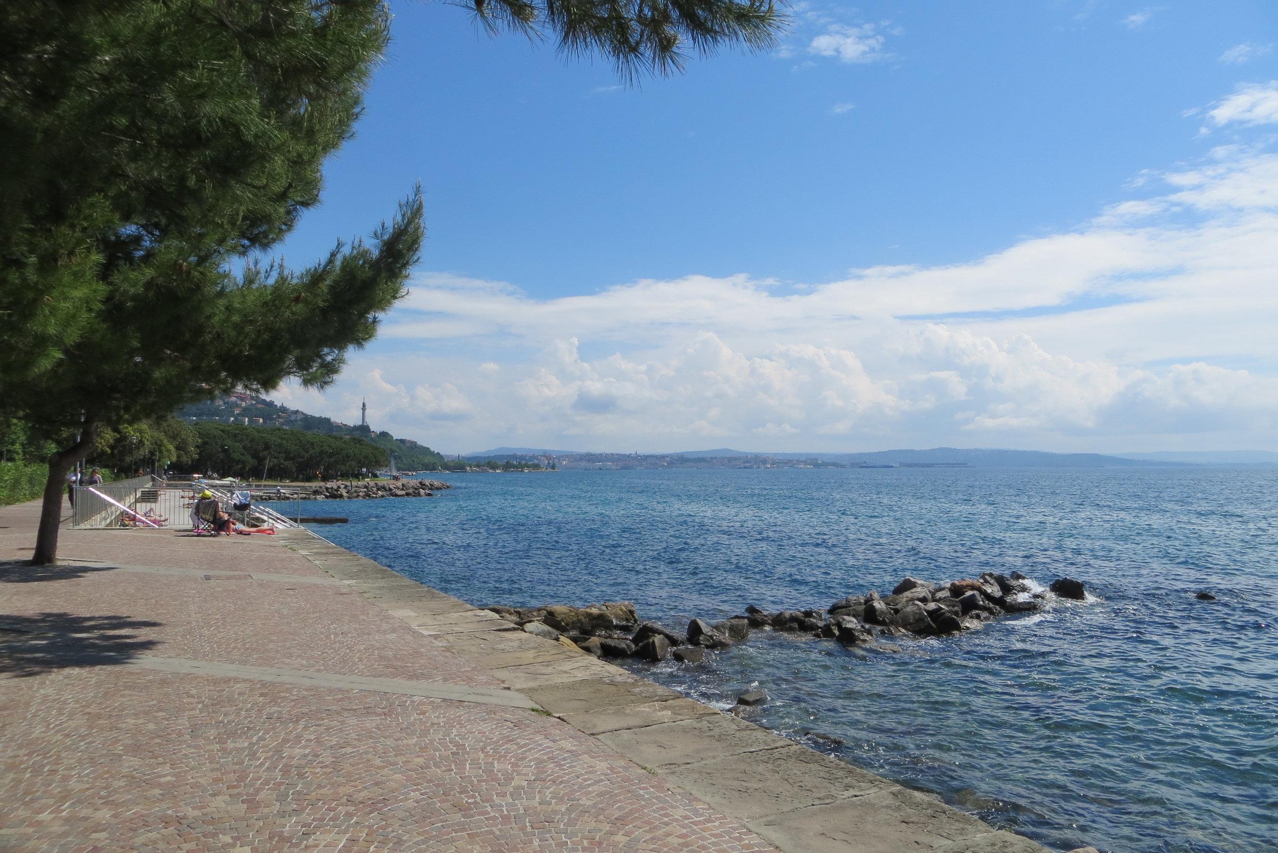 Trieste's Barcola facing the city, with the Faro della Vittora in the distance