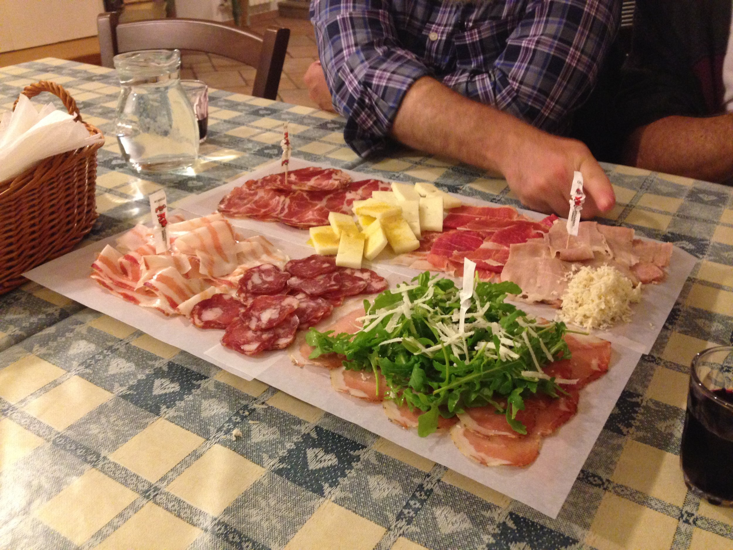A typical dinner at an osmiza, with salami, prosciutto crudo and cotto, cheese, rucola, horseradish, bread, and wine all produced at the farm